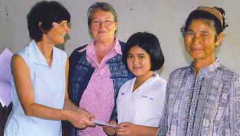 From left to right: Ricky Op de Laak, volunteer, Cory Croymans-Plaghki of the New Life Foundation, Nielawan Booblah, one of the orphaned scholarship recipients and her grandmother.
